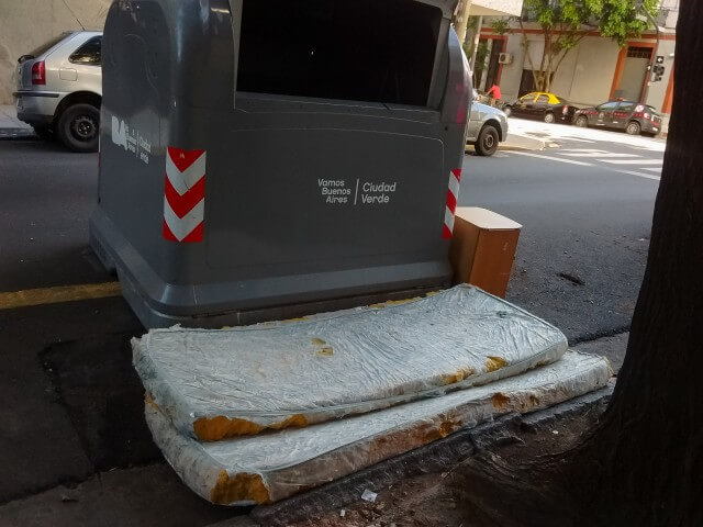 mattress-thrown-on-street-in-front-of-a-dumpster